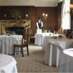 The beautiful dining room draped with white tablecloths where afternoon tea is served at Gravetye Manor, East Grinstead.