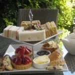 Perfect cut finger sandwiches, strawberry tarts and an assortment of cakes served on the outdoor terrace at Moor Hall Hotel and Spa, the perfect location for an al fresco afternoon tea in West Midlands.