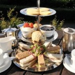 A beautiful three tiered cake stand set with finger sandwiches, scones and cakes for afternoon tea in Powys at the Lake Vyrnwy Hotela and Spa