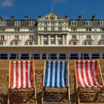Striped deck chairs on the beach in front of the majestic Royal Victoria Hotel, St Leonards on Sea, East Sussex. The perfect venue for an afternoon tea treat.