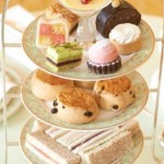 A traditional cake stand with finger sandwiches, scones and cakes for afternoon tea in Mayfair at Grosvenor House.