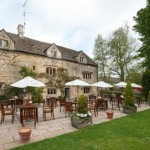 The outside terrace with tables and parasoles, set for outdoors afternoon tea at the Slaughters Country Inn, Gloucester.