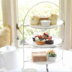 Afternoon tea in Bath. A beautiful three tiered cake stand with scones, finger sandwiches and cakes served in Tides Restaurant at Homewood Park, Bath.