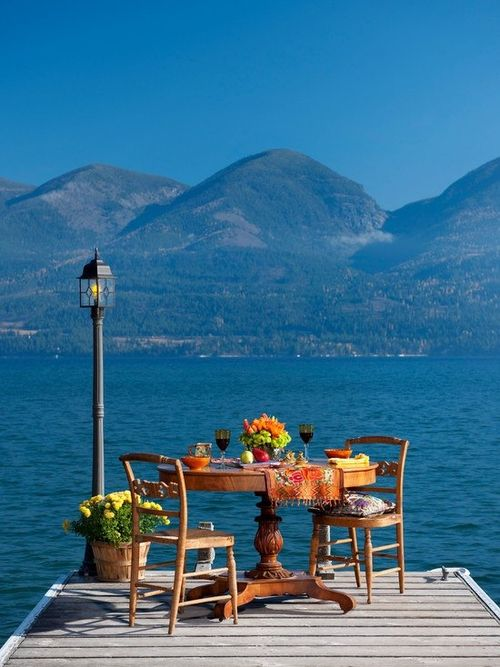 A jetty with table set for two with stunning views over a blue sea and mountains in the background