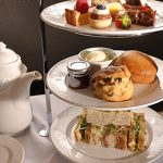 Decadent cake stand with finger cut sandwiches and scones with clotted cream and jam and delicate, bite size cakes - afternoon tea at the Vermont Hotel, Newcastle Upon Tyne