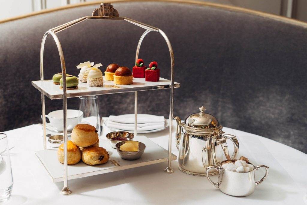 A beautiful cake stand with a d elicious selection of cakes, pastries and scones ready for Afternoon Tea at Harrods, London.