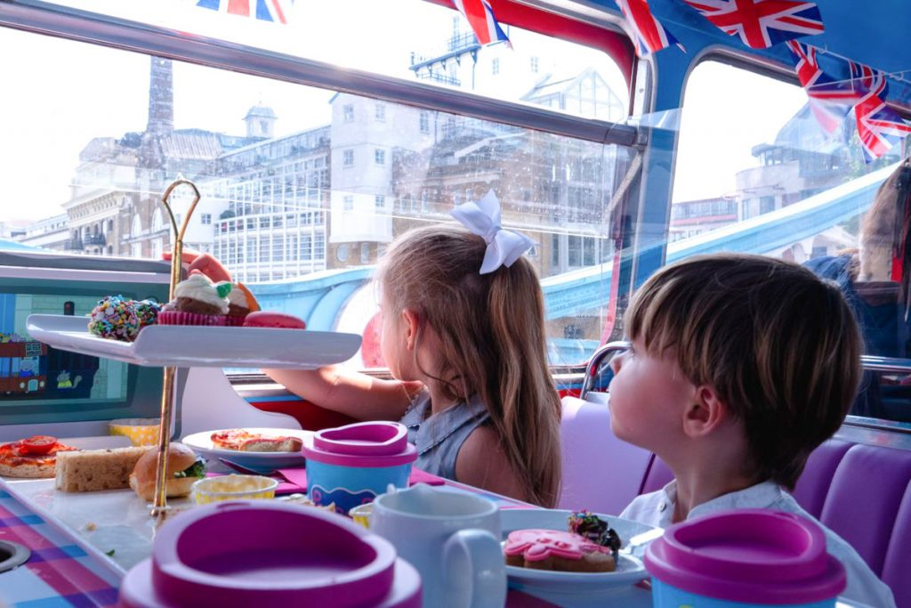Children enjoying their Peppa Pig Afternoon tea on board a London vintage red double decker bus.